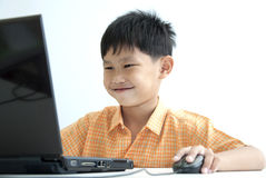 χρησιμοποίηση χαμόγελου υπολογιστών αγοριών Στοκ Φωτογραφίες
