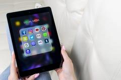Χρησιμοποίηση χεριών γυναικών iPad υπέρ με τα εικονίδια των κοινωνικών μέσων facebook, instagram, πειραχτήρι, google εφαρμογή στη Στοκ Φωτογραφία
