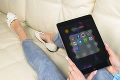 Χρησιμοποίηση χεριών γυναικών iPad υπέρ με τα εικονίδια των κοινωνικών μέσων facebook, instagram, πειραχτήρι, google εφαρμογή στη Στοκ Φωτογραφίες
