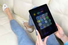 Χρησιμοποίηση χεριών γυναικών iPad υπέρ με τα εικονίδια των κοινωνικών μέσων facebook, instagram, πειραχτήρι, google εφαρμογή στη Στοκ Εικόνα