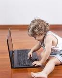 χρησιμοποίηση lap-top κοριτσιών υπολογιστών μωρών Στοκ εικόνες με δικαίωμα ελεύθερης χρήσης