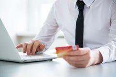 χρησιμοποίηση lap-top πιστωτική& Στοκ Εικόνα