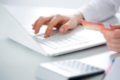 χρησιμοποίηση lap-top πιστωτική& Στοκ Εικόνες