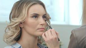 Χρησιμοποίηση makeup της βούρτσας για να εφαρμόσει τις σκιές ματιών Στοκ Φωτογραφίες