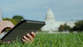 Χρησιμοποιήστε την ταμπλέτα στο υπόβαθρο του Capitol, στο πλαίσιο μπορείτε να δείτε μόνο τα χέρια Τουρισμός, μελέτη και ταξίδι γύ απόθεμα βίντεο