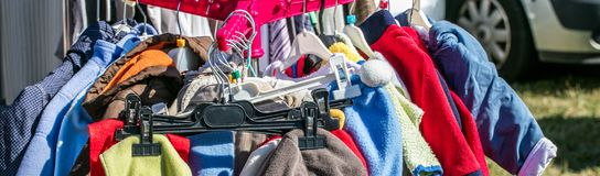 Χρησιμοποιημένα ενδύματα παιδιών και μωρών που επιδεικνύονται στο ράφι για την ανταλλαγή στοκ εικόνα με δικαίωμα ελεύθερης χρήσης