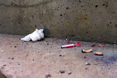 Χρησιμοποιημένη σύριγγα που ρίχνεται κάτω με τις άκρες τσιγάρων Τσιμεντένιο πάτωμα ρύπου Στοκ Φωτογραφία