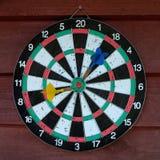 Χρησιμοποιημένος dartboard με δύο βέλη πέρα από το ξύλινο υπόβαθρο Στοκ φωτογραφίες με δικαίωμα ελεύθερης χρήσης