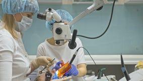 Χρησιμοποιημένο γιατρός μικροσκόπιο Ο οδοντίατρος θεραπεύει τον ασθενή στο σύγχρονο οδοντικό γραφείο Εργασία Orthodontist με το β φιλμ μικρού μήκους