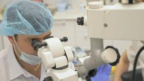 Χρησιμοποιημένο γιατρός μικροσκόπιο Ο οδοντίατρος θεραπεύει τον ασθενή στο σύγχρονο οδοντικό γραφείο Εργασία Orthodontist με το β απόθεμα βίντεο