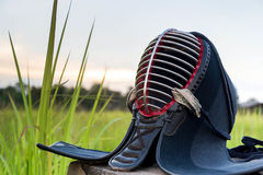 Χρησιμοποιημένο και βρώμικο κράνος ή άτομα Kendo στον τομέα χλόης στο υπόβαθρο ηλιοβασιλέματος Στοκ Εικόνα
