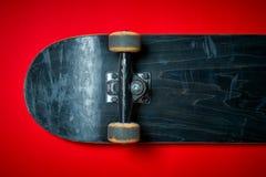 Χρησιμοποιημένο skateboard σε ένα κόκκινο υπόβαθρο Στοκ Εικόνα