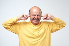 Χρησιμοποιώντας τα φυσικά earplugs για να μην ακούσει τις αεροτομές Όμορφο ευτυχές ώριμο ευρωπαϊκό άτομο που χαμογελά με τις ιδια στοκ εικόνα με δικαίωμα ελεύθερης χρήσης