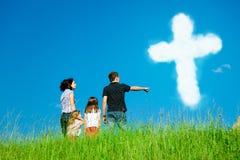 Χριστιανική οικογένεια που εξετάζει τα σύννεφα που διαμορφώνουν τον ιερό σταυρό Στοκ Φωτογραφία