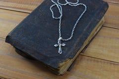 Χριστιανικός σταυρός με την παλαιά ιερή Βίβλο στον πίνακα Στοκ Εικόνες