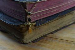 Χριστιανικός σταυρός με την παλαιά ιερή Βίβλο στον πίνακα Στοκ Φωτογραφίες