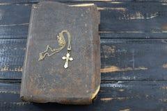 Χριστιανικός σταυρός με την παλαιά ιερή Βίβλο στον πίνακα Στοκ Φωτογραφία