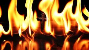 Χριστιανικός σταυρός συμβόλων θρησκείας στην πυρκαγιά κόλασης φιλμ μικρού μήκους