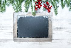 Χριστουγέννων κόκκινα μούρα κλάδων δέντρων διακοσμήσεων αειθαλή chalkboar Στοκ φωτογραφία με δικαίωμα ελεύθερης χρήσης
