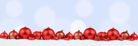 Χριστουγέννων σφαιρών εμβλημάτων κόκκινο χιόνι υποβάθρου διακοσμήσεων ανοικτό μπλε Στοκ φωτογραφία με δικαίωμα ελεύθερης χρήσης