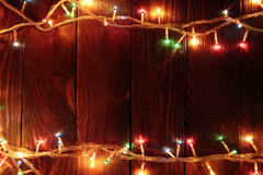 Χριστουγέννων φω'τα γιρλαντών πυράκτωσης ζωηρόχρωμα στο ξύλινο αγροτικό backg Στοκ Φωτογραφίες