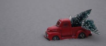 Χριστουγεννιάτικα δέντρα φόρτωσης ανοιχτών φορτηγών παιχνιδιών στο χιόνι στοκ φωτογραφία