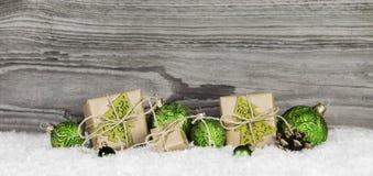 Χριστουγεννιάτικα δώρα και πράσινες σφαίρες στο ξύλινο παλαιό γκρίζο υπόβαθρο Στοκ Εικόνες