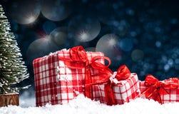 Χριστουγεννιάτικα δώρα με τα κόκκινα τόξα στο χιόνι Στοκ Φωτογραφία