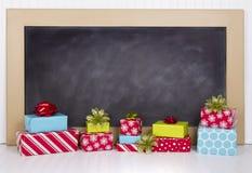 Χριστουγεννιάτικα δώρα με τον πίνακα κιμωλίας Στοκ εικόνες με δικαίωμα ελεύθερης χρήσης