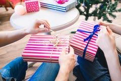 Χριστουγεννιάτικα δώρα που ανοίγουν κοντά στο δέντρο πεύκων Στοκ Εικόνες