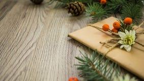 Χριστουγεννιάτικα δώρα που τυλίγονται στο έγγραφο του Κραφτ με τη φυσική διακόσμηση Άποψη γωνίας Στοκ Φωτογραφίες