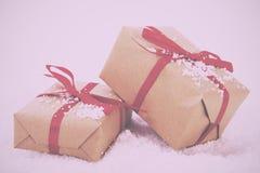 Χριστουγεννιάτικα δώρα στο καφετί έγγραφο με τον κόκκινο τρύγο κορδελλών αναδρομικό Στοκ Φωτογραφίες