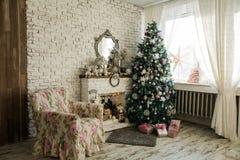 Χριστουγεννιάτικο δέντρο και εστία με μια πολυθρόνα Στοκ Φωτογραφία