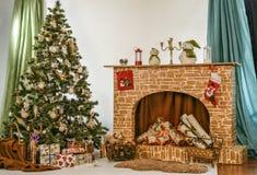 Χριστουγεννιάτικο δέντρο κοντά στην εστία στο δωμάτιο Στοκ Φωτογραφία