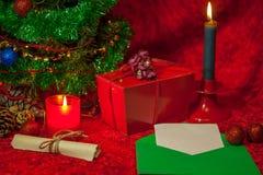 Χριστουγεννιάτικο δέντρο με τον ανοικτό φάκελο, το έγγραφο και το καίγοντας κερί Στοκ Φωτογραφίες
