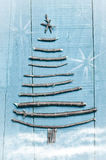 Χριστουγεννιάτικο δέντρο που γίνεται από τα ξηρά ραβδιά στο ξύλινο, μπλε υπόβαθρο Χιόνι και εικόνα χιονιού flaks Διακόσμηση χριστ Στοκ Φωτογραφία