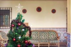 Χριστουγεννιάτικο δέντρο που διακοσμείται με τις σφαίρες και τις διακοσμήσεις Στοκ Εικόνες