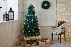 Χριστουγεννιάτικο δέντρο υποβάθρου, καρέκλα και στεφάνι Χριστουγέννων Στοκ Φωτογραφία