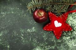 Χριστουγεννιάτικο δέντρο, διακόσμηση με ένα κόκκινο αστέρι και ένα μήλο σε ένα gre Στοκ Φωτογραφία