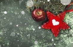 Χριστουγεννιάτικο δέντρο, διακόσμηση με ένα κόκκινο αστέρι και ένα μήλο σε ένα gre Στοκ εικόνα με δικαίωμα ελεύθερης χρήσης