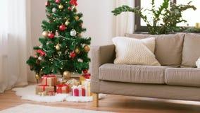 Χριστουγεννιάτικο δέντρο, δώρα και καναπές στο άνετο σπίτι απόθεμα βίντεο