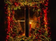 Χριστουγεννιάτικο δέντρο και εστία που βλέπουν μέσω ενός ξύλινου παραθύρου καμπινών στοκ φωτογραφία