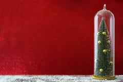 Χριστουγεννιάτικο δέντρο και χιόνι στο φωτεινό κόκκινο υπόβαθρο Στοκ εικόνα με δικαίωμα ελεύθερης χρήσης
