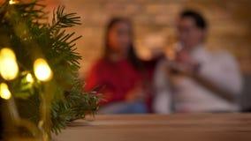 Χριστουγεννιάτικο δέντρο με τα φω'τα και τη θολωμένη νέα συνεδρίαση ζευγών στον καναπέ και την ομιλία στο υπόβαθρο απόθεμα βίντεο