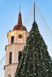 Χριστουγεννιάτικο δέντρο με τις διακοσμήσεις και πύργος κουδουνιών στο τετράγωνο καθεδρικών ναών Στοκ εικόνες με δικαίωμα ελεύθερης χρήσης