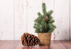 Χριστουγεννιάτικο δέντρο με τον κώνο πεύκων στο ξύλινο υπόβαθρο στοκ φωτογραφίες