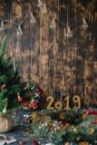 Χριστουγεννιάτικο δέντρο με τους χρυσούς αριθμούς 2019 σε ένα ξύλινο υπόβαθρο στοκ φωτογραφία