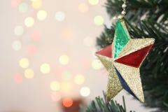 Χριστουγεννιάτικο δέντρο με το χρυσό αστέρι διακοσμήσεων με το φως bokeh backg στοκ εικόνες