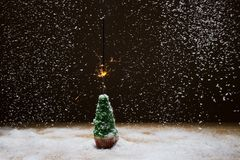 Χριστουγεννιάτικο δέντρο με το sparkler σε ένα υπόβαθρο του χιονιού απεικόνιση αποθεμάτων
