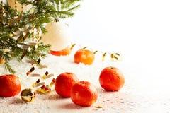Χριστουγεννιάτικο δέντρο με tangerines στο άσπρο υπόβαθρο χιονιού Στοκ Εικόνες